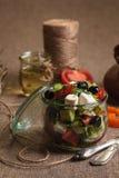 La ensalada griega sirvió en el tarro de cristal con los ingredientes Foto de archivo