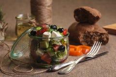 La ensalada griega sirvió en el tarro de cristal con los ingredientes Imágenes de archivo libres de regalías