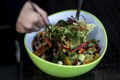 La ensalada sana fresca deliciosa en un cuenco verde se mezcló por las manos de una mujer con la comida de cuchara de la ensalada imagen de archivo libre de regalías