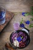 La ensalada vegetal púrpura en el cuenco negro colocado en la tabla de madera allí es cuchara, arroz negro, aliño de ensaladas, v fotos de archivo
