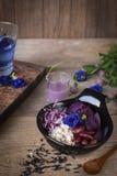 La ensalada vegetal púrpura en el cuenco negro colocado en la tabla de madera allí es cuchara, arroz negro, aliño de ensaladas, v fotografía de archivo