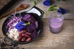 La ensalada vegetal p?rpura en el cuenco negro colocado en la tabla de madera all? es cuchara, arroz negro, ali?o de ensaladas y  fotografía de archivo libre de regalías