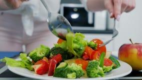 La ensalada vegetal sana con el aceite de oliva, manos con la bifurcación mezcla lechuga con los tomates y los pepinos almacen de video