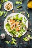 La ensalada verde del pollo sirvió en la tabla rústica con las nueces de pino y la preparación del aceite Foto de archivo libre de regalías