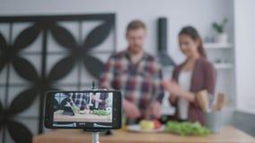 La enseñanza de Internet para cocinar la comida vegetariana, los bloggers mujer y el hombre enseñan a los seguidores a cocinar la almacen de metraje de vídeo