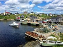 La ensenada, Nova Scotia, el puerto, los barcos y las casas de Peggy en verano Fotos de archivo
