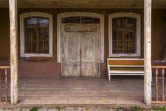 La entrada a la casa de madera vieja, el sofá viejo está en el mirador foto de archivo