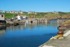 La entrada, los barcos y el pueblo de puerto en St. Abbs, Berwickshir imagen de archivo libre de regalías
