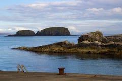 La entrada rocosa al pequeño puerto en Ballintoy en la costa del norte de Antrim de Irlanda del Norte en un día de primavera tran foto de archivo