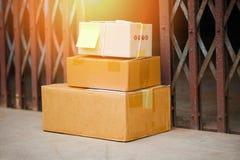 La entrega del comercio electrónico que hacía compras en línea y la orden entregaron paquetes en piso cerca del acero de la puert imagen de archivo
