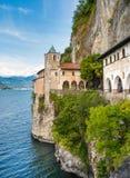 La ermita de Santa Caterina del Sasso es cara de la roca que sobresale por directamente el lago Maggiore Imagenes de archivo