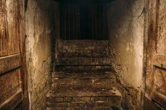 La escalera de madera espeluznante del grunge sucio del sótano abandonado, lugar donde vive el vagabundo, sale a la calle oscura imagen de archivo