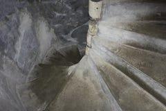 La escalera espiral vieja, pedregosa, un castillo o fortaleza, entra abajo oscuridad espeluznante fotos de archivo libres de regalías
