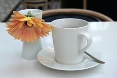 La escena de invitación con la taza simple y el platillo del café con leche, escoge la flor como recepción a la mañana fotos de archivo