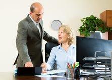 La escena de la oficina con dos envejeció y los trabajadores positivos Imágenes de archivo libres de regalías