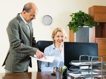 La escena de la oficina con dos envejeció y los trabajadores serios Imagenes de archivo