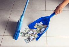 La escoba de la mujer barre dólares en cucharada de la basura en fondo del piso imagenes de archivo