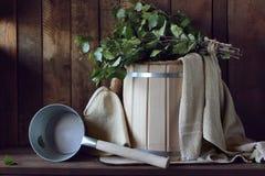 La escoba del baño hecha de abedul y el baño de madera bucket en un palo ruso Foto de archivo libre de regalías
