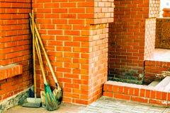 La escoba y las palas que el ` s del limpiador equipa después de limpiar en la yarda en la calle Fotos de archivo