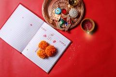 La escritura de la caligrafía en Shubha Labh hindi significa calidad y riqueza, sobre el cuaderno que considera rojo, diya, fotografía de archivo