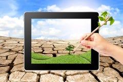 La escritura de la mano piensa la ecología verde en la tablilla Imagen de archivo