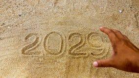 La escritura del año en la arena con el primero plano de borroso alcanza hacia fuera a Han Foto de archivo