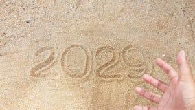 La escritura del año en la arena con el primero plano de borroso alcanza hacia fuera a Han Imagen de archivo libre de regalías