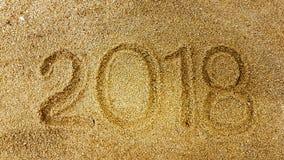 La escritura del año en la arena de oro con shellsea Foto de archivo libre de regalías
