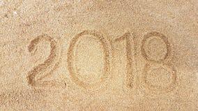 La escritura del año en la arena de oro con shellsea Foto de archivo