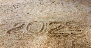 La escritura del año en la arena de oro con shellsea Fotos de archivo