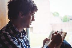 La escritura del estudiante observa cerca de ventana Fotografía de archivo