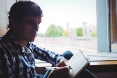 La escritura del estudiante observa cerca de ventana Fotografía de archivo libre de regalías
