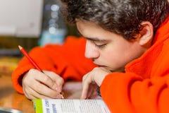 La escritura del muchacho con rojo y se corrige Foto de archivo libre de regalías