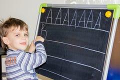 La escritura del muchacho pone letras a aprender al niño elegante del hijo de los procces Fotografía de archivo