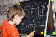 La escritura del muchacho pone letras a aprender al niño elegante del hijo de los procces Foto de archivo libre de regalías