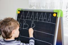 La escritura del muchacho pone letras a aprender al niño elegante del hijo de los procces Foto de archivo