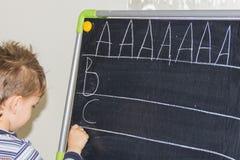 La escritura del muchacho pone letras a aprender al niño elegante del hijo de los procces Imagen de archivo libre de regalías