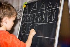 La escritura del muchacho pone letras a aprender al niño elegante del hijo de los procces Fotos de archivo libres de regalías