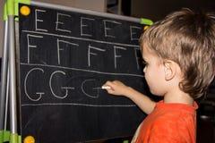 La escritura del muchacho pone letras a aprender al niño elegante del hijo de los procces Imagenes de archivo
