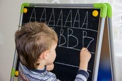 La escritura del muchacho pone letras a conocimiento del proceso de aprendizaje del pequeño niño Foto de archivo libre de regalías