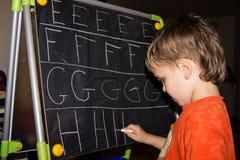 La escritura del muchacho pone letras a conocimiento del proceso de aprendizaje del pequeño niño Fotografía de archivo libre de regalías