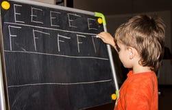 La escritura del muchacho pone letras a conocimiento del proceso de aprendizaje del pequeño niño Fotografía de archivo