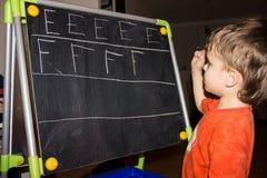 La escritura del muchacho pone letras a conocimiento del proceso de aprendizaje del pequeño niño Fotos de archivo