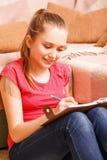 La escritura joven de la muchacha del adolescente en diario se sienta en piso Foto de archivo