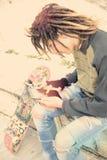 La escritura joven del individuo del rasta en tonos calientes de una tableta se aplicó Fotos de archivo libres de regalías