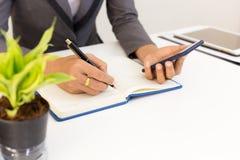 La escritura y el uso del hombre de negocios llaman por teléfono en el cepillado de madera de la tabla, de las finanzas del conce foto de archivo libre de regalías