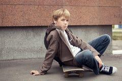 La escuela adolescente se sienta en el patín cerca de escuela Imagen de archivo libre de regalías