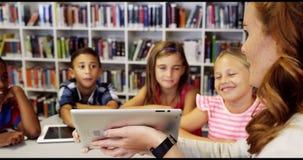 La escuela de enseñanza del profesor embroma en la tableta digital en biblioteca