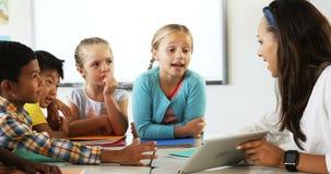 La escuela de enseñanza del profesor embroma en la tableta digital en sala de clase