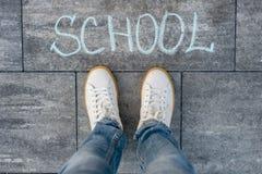 La escuela de la palabra en el asfalto y los pies del estudiante Imagen de archivo